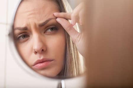 close-up van de jonge vrouw in de spiegel kijken. spiegeling van mooi meisje wenkbrauw Stockfoto