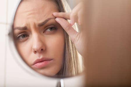closeup of young woman looking into mirror. mirror reflection of beautiful girl eyebrow