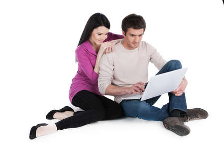 young man and woman sitting on floor. beautiful girl leaning on man shoulder and watching photo