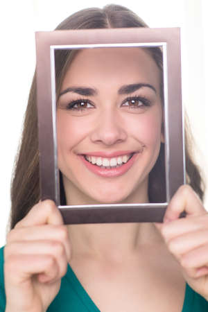 young attractive woman holding frame. closeup portrait of girl behind paper frame photo