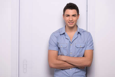 young attractive man standing straight. handsome man leaning against door photo