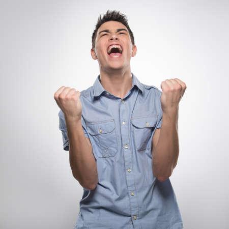 attractive male: apuesto joven grita de alegr�a. hombre atractivo muestra las manos y los pu�os Foto de archivo