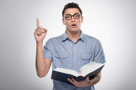 handsome young man standing and talking. attractive male opening book and teaching photo