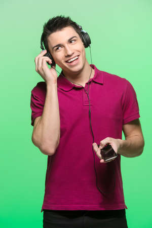 red tshirt: attractive young man listening music. handsome male wearing headphone and red t-shirt