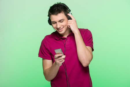 tuning: handsome young man standing and listening music. Attractive male holding headphones and player