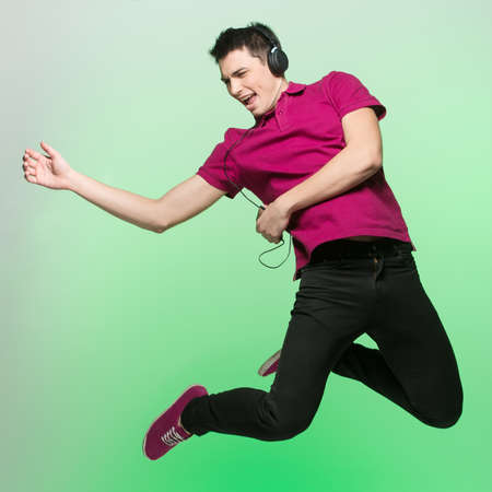 air guitar: positive young man jumping and singing. handsome male in red listening music Stock Photo