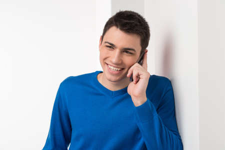 frienship: attractive young man talking on phone. handsome male in blue leaning against wall