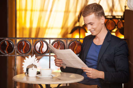 young man reading newspaper in cafe. handsome guy sitting and drinking coffee photo