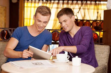 amigas conversando: dos chicos jóvenes, hablando en café. hombre guapo que sostiene la tablilla y escuchar