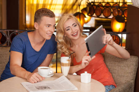 beautiful blond girl holding tablet. handsome guy looking at screen and smiling photo