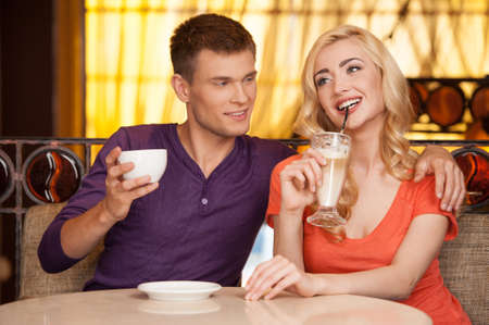 man hugging woman in cafe and smiling. beautiful girl sitting on couch and drinking latte photo