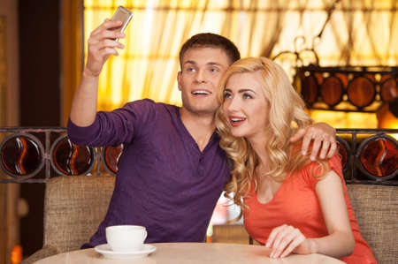 beautiful couple making photo in cafe. man hugging woman and holding cell phone photo