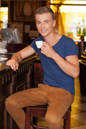 handsome guy sitting and drinking espresso. young man holding cup and smiling photo