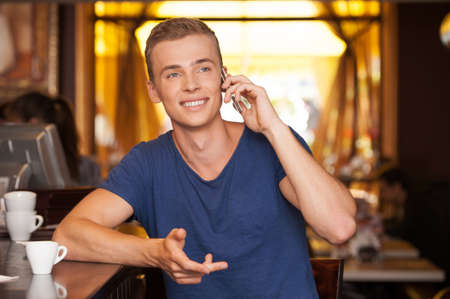 young handsome man talking on phone. handsome guy sitting in cafe and smiling photo