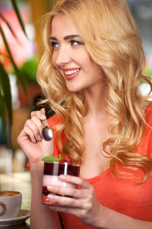 happy young girl eating jelly. beautiful woman sitting in cafe and smiling photo