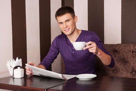 young man sitting and drinking coffee. handsome boy reading newspaper in cafe photo