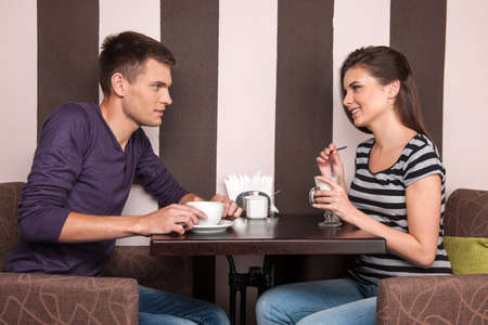 young man and woman talking in coffee shop. pretty girl and boy drinking coffee photo