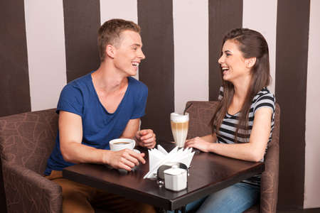 young girl and boy laughing in cafe. beautiful man and woman drinking coffee photo