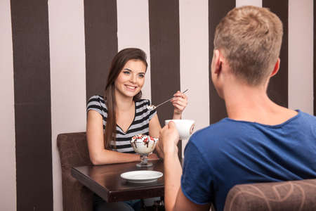 young couple sitting and talking in cafe. handsome man drinking coffee and looking at girl photo