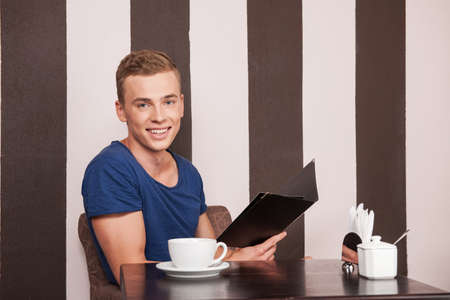 young man sitting in cafe and smiling. handsome boy picking up check for coffee photo