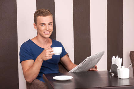 young man sitting in cafe and reading. handsome guy reading and drinking coffee photo