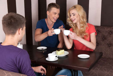 people drinking coffee: three young people drinking coffee. handsome man flirting with beautiful girl