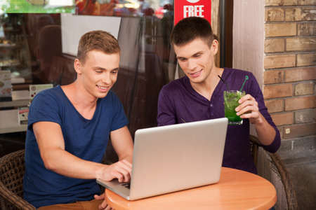 hot guy: two man working on computer in cafe. handsome guy drinking and looking at screen Stock Photo