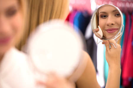 round face: beautiful young woman looking into mirror. Attractive blond girl cleaning face