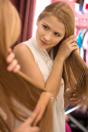 beautiful young girl combing hair. attractive blond woman looking into mirror photo