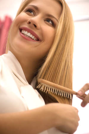 happy young girl combing hair. beautiful blond lady smiling and laughing photo