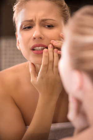 naked girl touching acne on face. beautiful woman in bathroom frowning and upset photo
