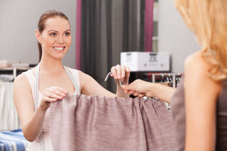 suggesting: seller suggesting tissue to customer and smiling. back view of blond buyer holding fabric