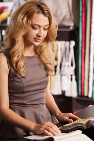 proprietor: beautiful blond girl selecting color. attractive lady sitting in store and smiling