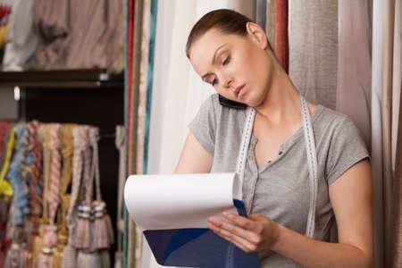 mooie brunette praten over de telefoon en schrijven. aantrekkelijke vrouw in gordijnen winkel