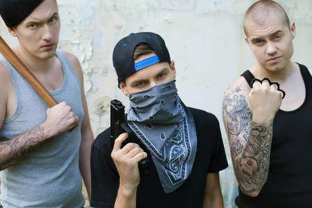 Trois gangsters avec des armes à la recherche dans la caméra. criminels tenant une batte de baseball, pistolet et articulations Banque d'images - 29469417