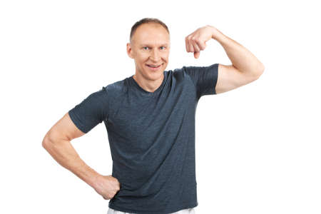 older man flexing muscles and smiling. caucasian guy standing on white and showing off photo