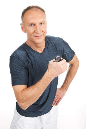 forearm: aged man squeezing gripper and training. man standing with gripper on white background.