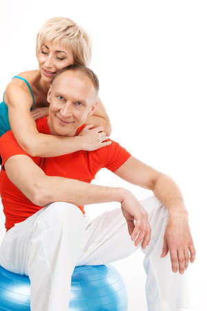 beautiful blond lady hugging aged man. male sitting on fitness ball and smiling photo