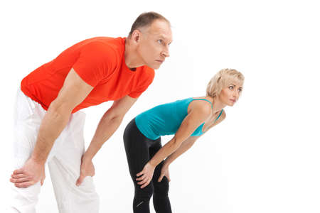 man legs: man and woman stretching on white background. side view of aged couple warming
