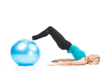 aged lady workout on white background. blond woman with legs on fitness ball photo
