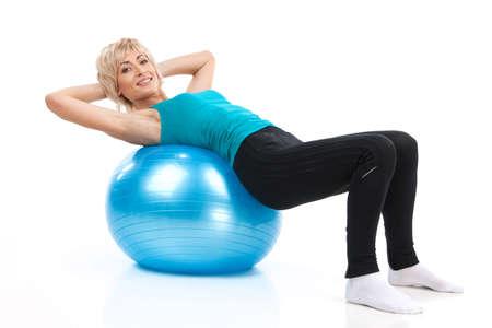 高齢者女性フィットネス ボールの上に横たわる。白い背景で金髪の女性運動