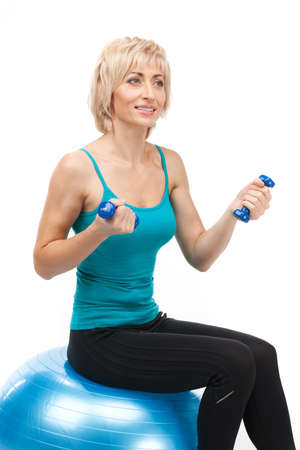 40 50: aged woman holding dumbbells and smiling. blond lady sitting on fitness ball Stock Photo