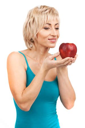 waist up: blond woman holding red apple. aged lady smiling waist up on white background Stock Photo
