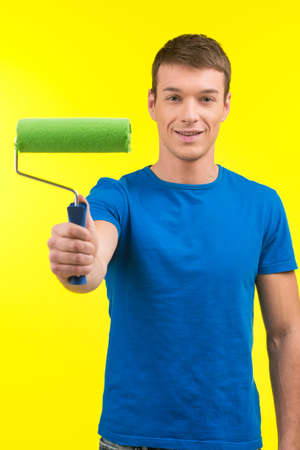 man painting: man holding paint roller and smiling. young handsome guy painting on yellow background