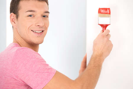 man painting: man painting wall using red color. closeup view of guy decorating house