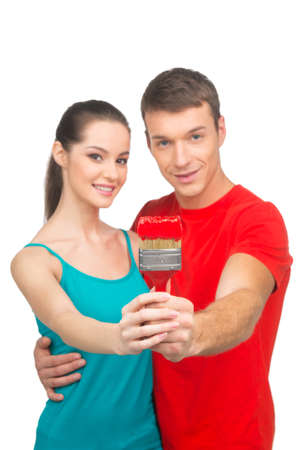 young couple smiling: young couple holding paintbrush together. boy hugging girl on white background