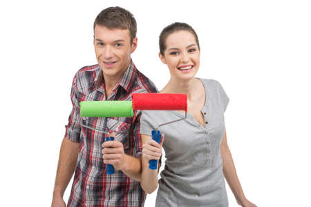 beautiful couple holding painting roller. man and woman standing on white background and smiling 版權商用圖片