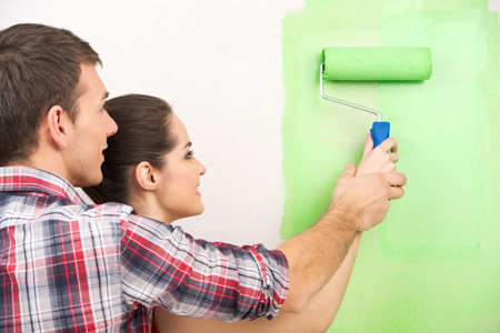 hombre pintando: el hombre ayuda a la mujer de la pintura de la pared. pareja hermosa celebración de rodillos de pintura juntos Foto de archivo