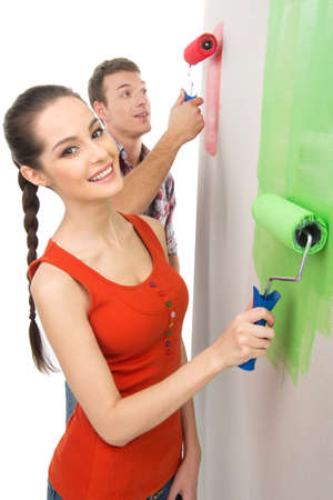wall painting: beautiful girl painting wall and smiling. couple using painting roller to color wall Stock Photo