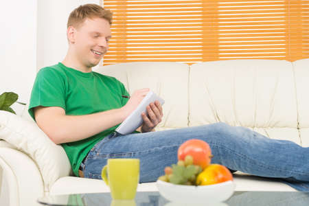 noting: man sitting on couch and writing letter. young man resting at home and smiling Stock Photo